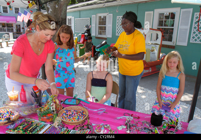 Massachusetts Cape Cod Hyannis Main Street Black woman braiding beading beads girl mother sisters family - Stock Image