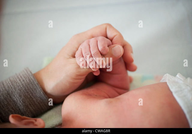 Mother holding newborn baby's hand - Stock-Bilder