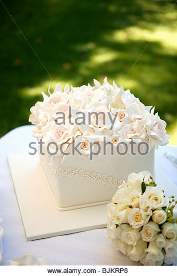 Square wedding cake with a mass of roses - Stock Image