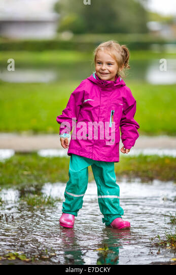 Happy little girl plays in a puddle - Stock Image