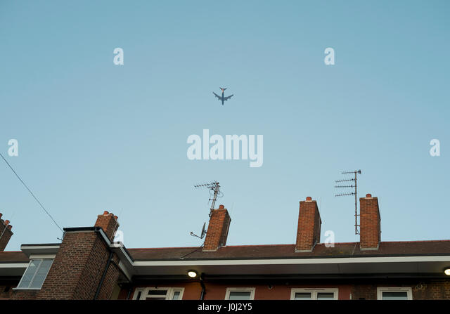 A plane files across rooftops of a block of flats in Londons Bethnal Green - Stock Image