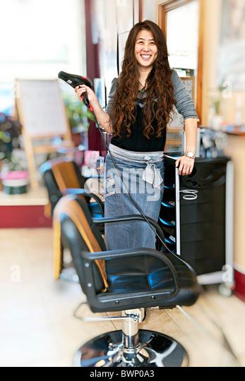 Happy hairdresser holding hairdryer in hair salon - Stock Image