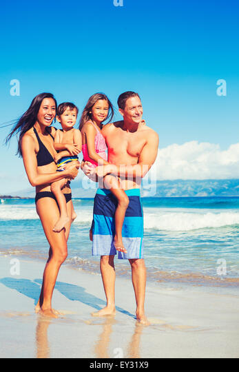 Portrait of Young Happy Family Having Fun at the Beach Outdoors - Stock Image