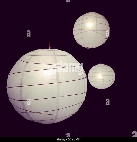 Three lights hanging in darkness from ceiling. - Stock Image