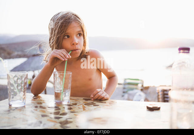 Boy having drink at lakeside - Stock Image