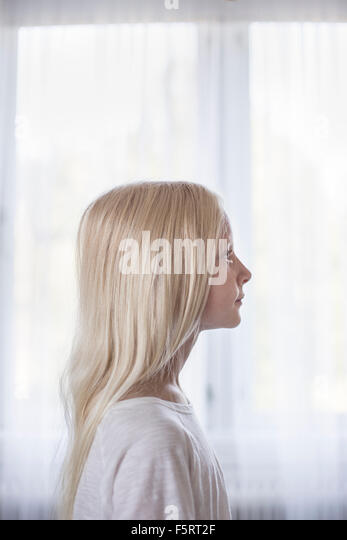 Sweden, Side view of blonde girl (10-11) in front of white curtains - Stock Image