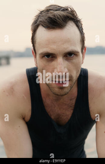 Close up portrait of young male runner on riverside - Stock Image