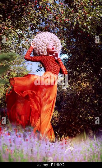 Creativity. Ultramodern Woman Blond in Artificial Huge Futuristic Wig Outside - Stock Image