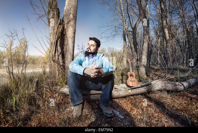 Man in blue shirt with bow tie and ukulele on the tree trunk in the forest - Stock Image