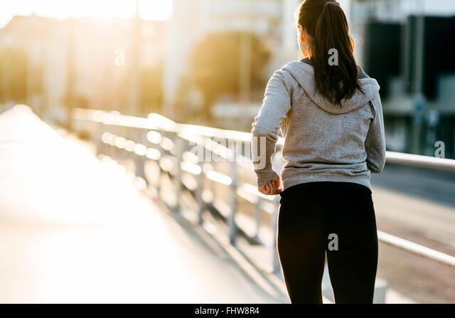 Beautiful female jogging in city and keeping her body in shape - Stock Image