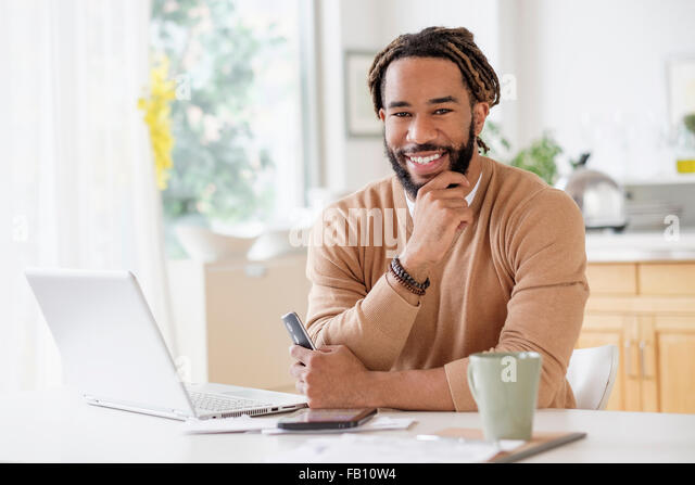 Portrait of smiley young man with laptop at table - Stock-Bilder