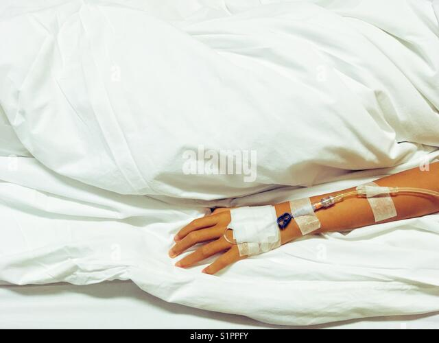 Arm of small Asian girl with injection of medicine drop counter in Hospital room on bed - Stock Image