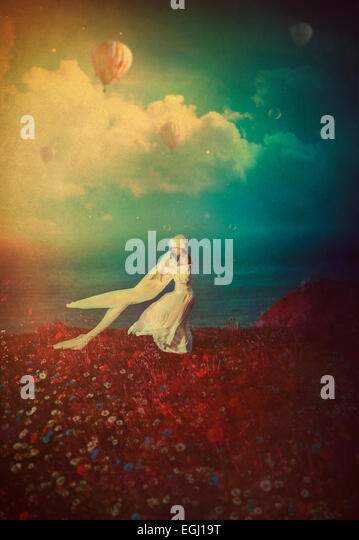 young woman in white dress dancing on the cliff - Stock-Bilder