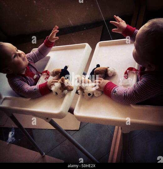 Baby boy is playing with his mirror reflection - Stock Image