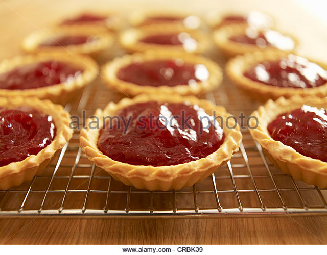 Close up of jam tarts cooling on wire rack - Stock Image