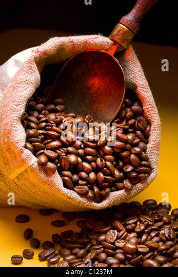 Sack of coffee beans and scoop. On a dark yellow background. - Stock Image