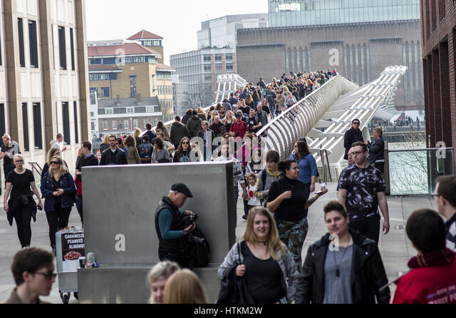 London Millenium Bridge filled with people crossing the Thames River on a busy sunny weekend in March 2017 - Stock Image