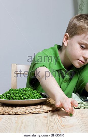 Boy with peas - Stock Image