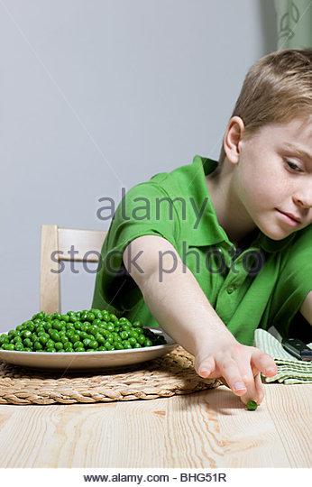 Boy with peas - Stock Image