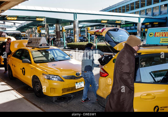 New York City NY NYC Queens LaGuardia Airport LGA outside taxi cab picking up passenger - Stock Image