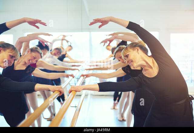 Cheerful mature ballerinas stretching with hands up standing at mirror in ballet class. - Stock Image