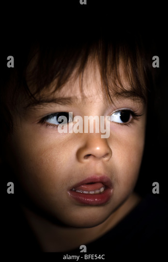 2 1/2 year old boy with dramatic lighting and looking apprehensive, Montreal, Quebec, Canada - Stock Image