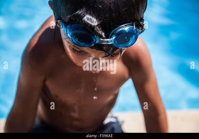 Boy getting out of swimming pool - Stock Image