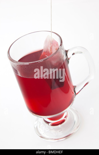 Glass of fruit tea with a teabag brewing isolated on a plain white background. England UK Britain - Stock Image