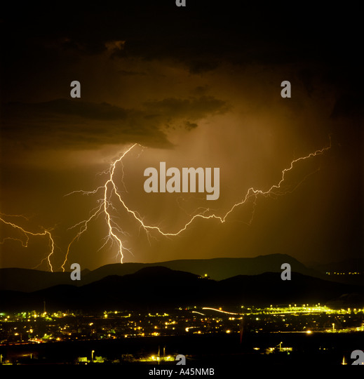 Lightning  bolts strike from a dark and stormy sky over the glowing cityscape of Tucson Arizona. USA - Stock Image