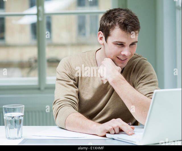 Young businessman using laptop at desk in office - Stock-Bilder