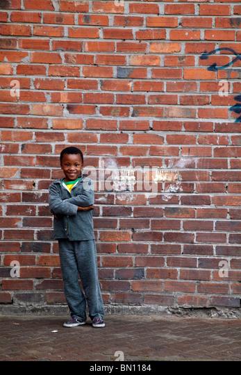 black boy against brick wall in township South Africa - Stock-Bilder