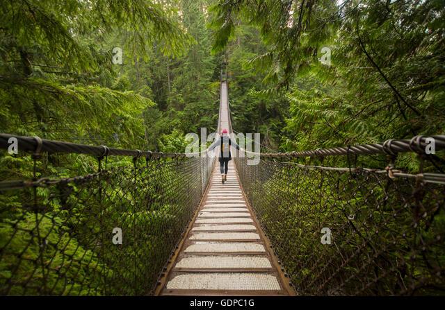 Woman on Lynn canyon suspension bridge, North Vancouver, British Columbia, Canada - Stock Image