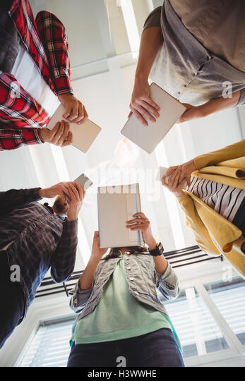 Directly below shot of business people using technologies - Stock Image