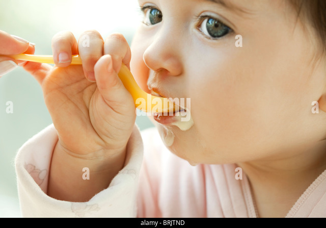 Infant learning to eat with a spoon - Stock-Bilder
