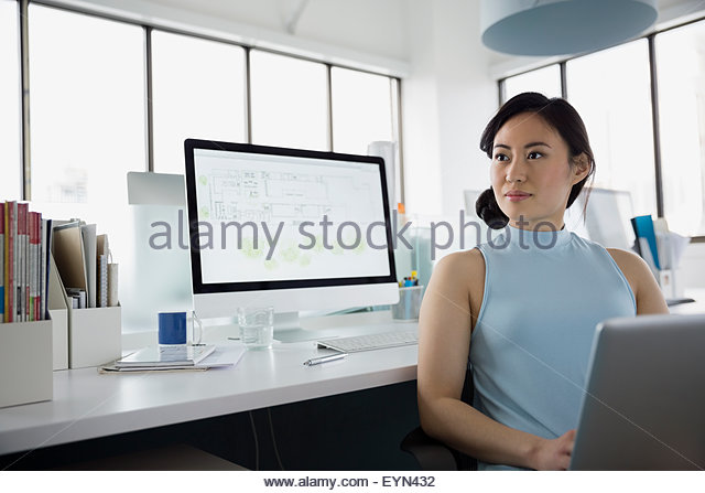 Pensive architect working at laptop and computer office - Stock Image