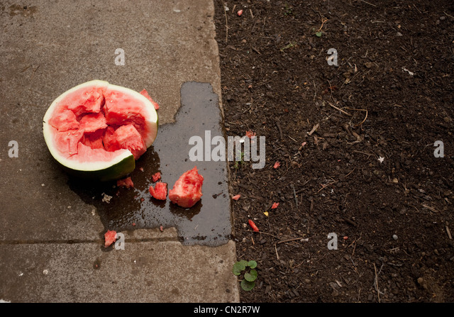 Broken watermelon on sidewalk - Stock Image