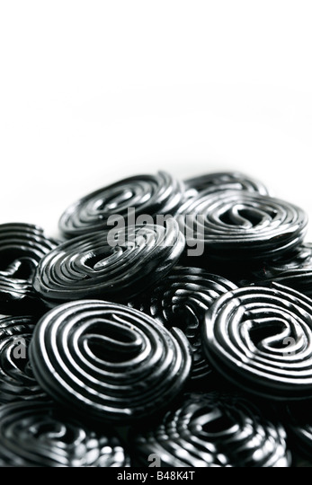 Rolls of tasty liquorice candy rolls isolated on white - Stock Image