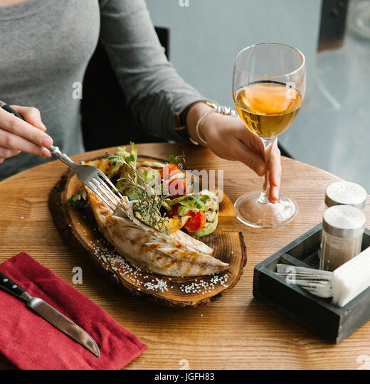 Woman eating fish with white wine - Stock Image
