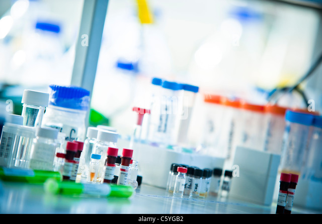 glass test tubes with colored tops on bench side in science laboratory - Stock Image