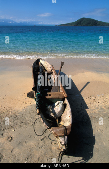 Honduras Bay Islands Garifuna canoe wooden dugout Los Cochinos vertical sail folded in boat paddle - Stock Image