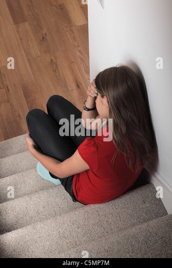 Depressed girl sitting on the stairs alone hand on head - Stock Image