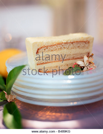 A SLice of Triple Layer Lemon Cake on a Stack of Plates - Stock Image