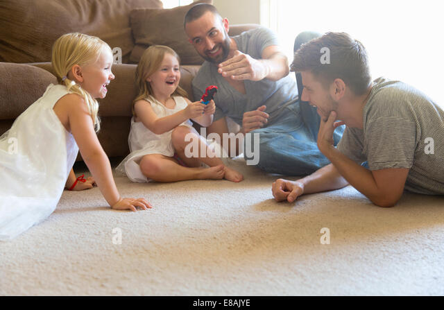 Male couple and two daughters playing on sitting room floor - Stock-Bilder