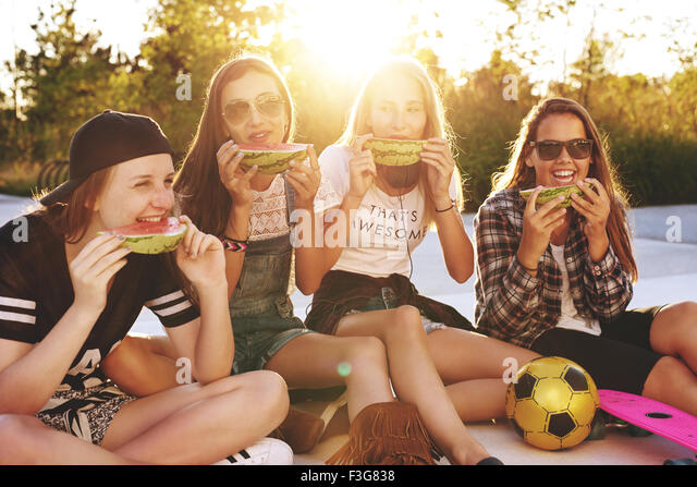Teenage girls hanging out in a park on a summer evening - Stock-Bilder