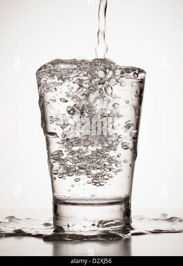 Water overflowing from glass - Stock Image