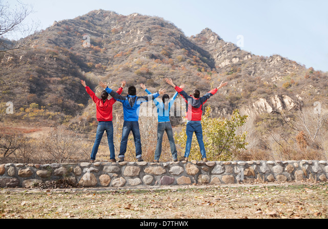 Group of young people standing on the ledge, arms outstretched - Stock Image