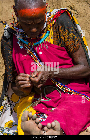 Maasai woman wearing traditional attire weaves beaded jewelry in a village near the Masai Mara, Kenya, East Africa - Stock Image