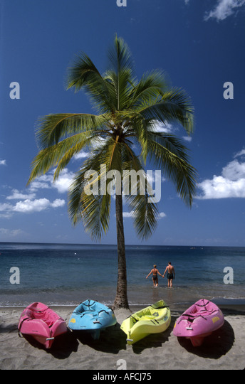 West Indies St. Lucia Anse Chastanet Resort rental kayaks palm tree Caribbean Sea shore couple wading - Stock Image