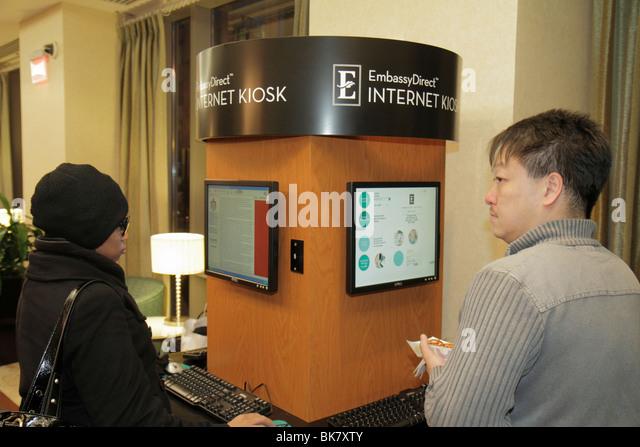 Washington DC 10th Street NW Embassy Suites Hotel lodging Internet Kiosk Asian Black man woman keyboard screen guest - Stock Image