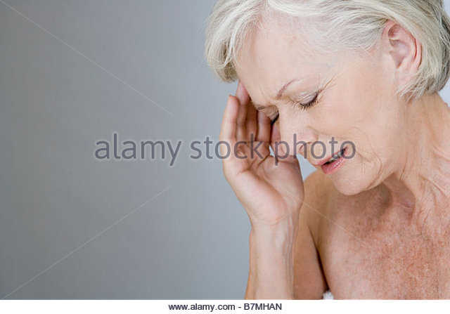 A senior woman with a headache, touching temple - Stock Image
